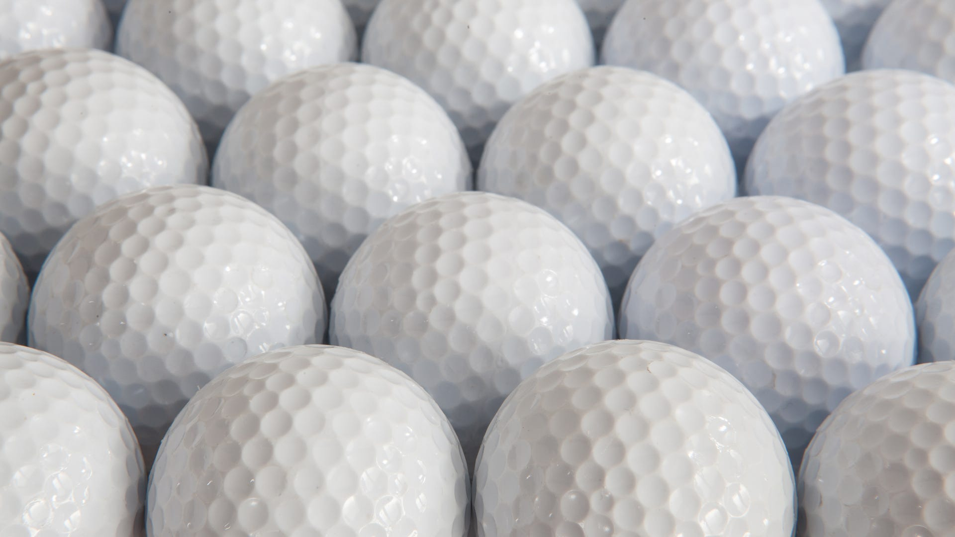 White golf balls lined up in a box.