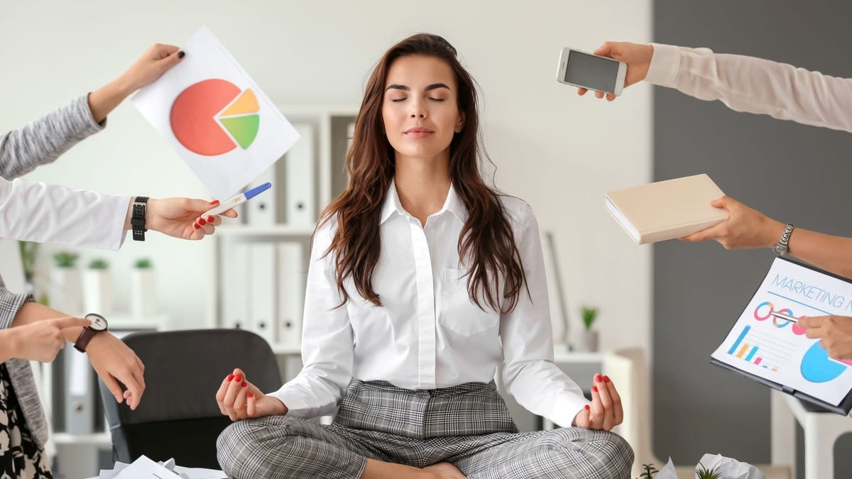 A woman meditating on a desk while extended arms hold out various work items to her, including graphs and phones.