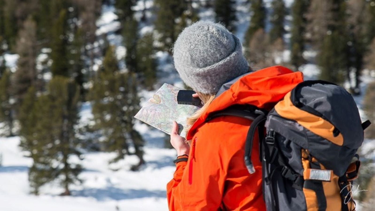 A man on a hike using a Suunto MC-2 compass and a map.