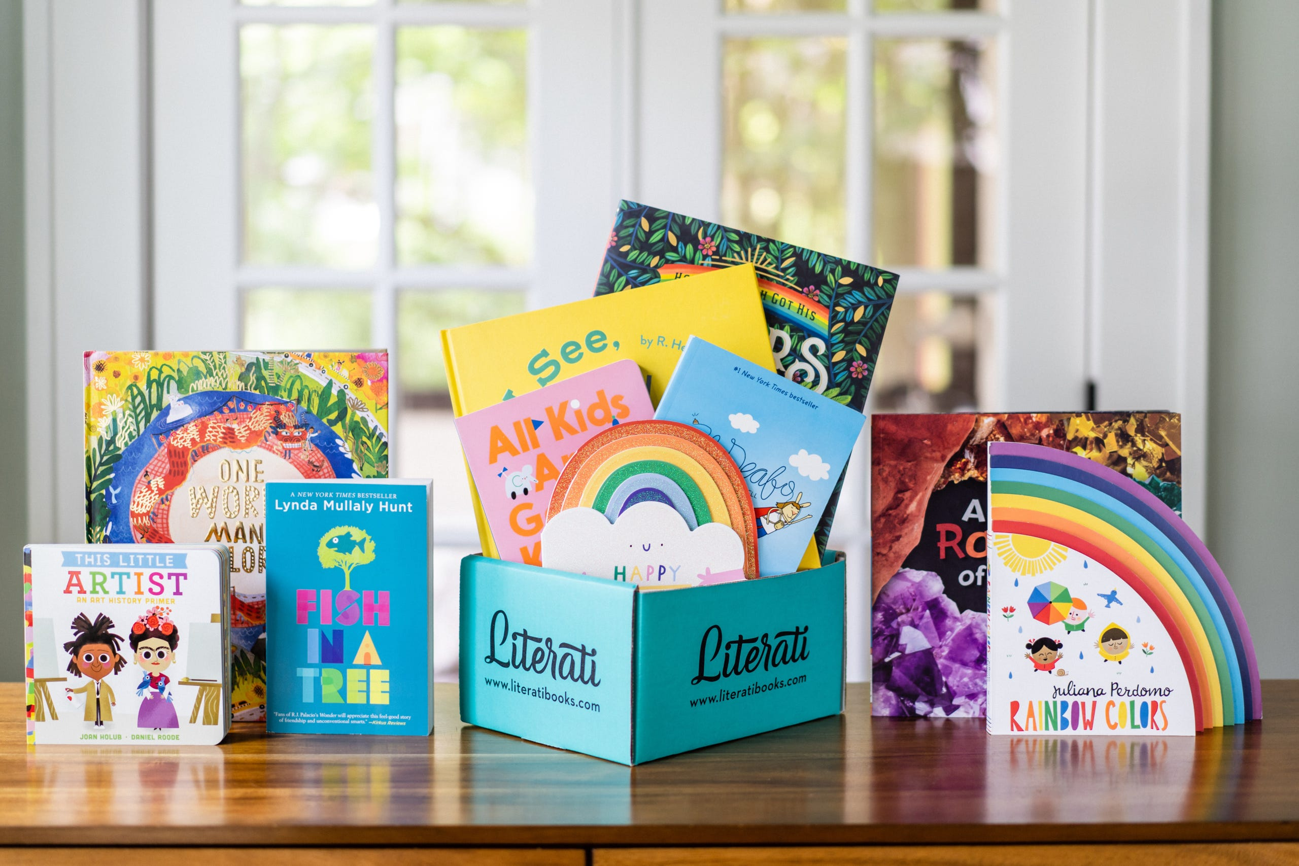Several colorful children's books displayed on a wood tabletop in front of a window