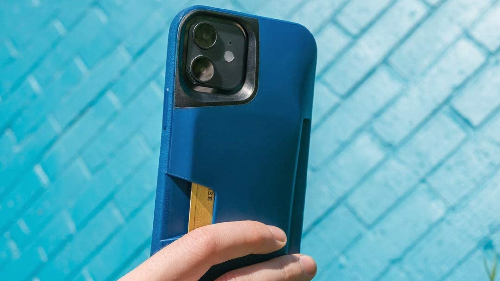 A hand holds an iPhone that's in a blue wallet case.
