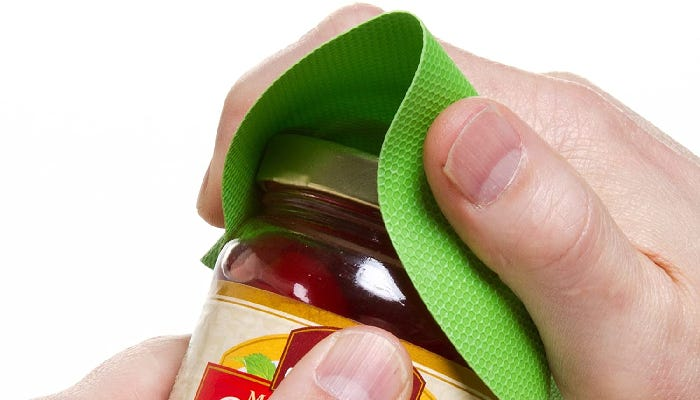 A left hand holds a jar and a right hand is shown twisting the jar lid with a green jar gripper.