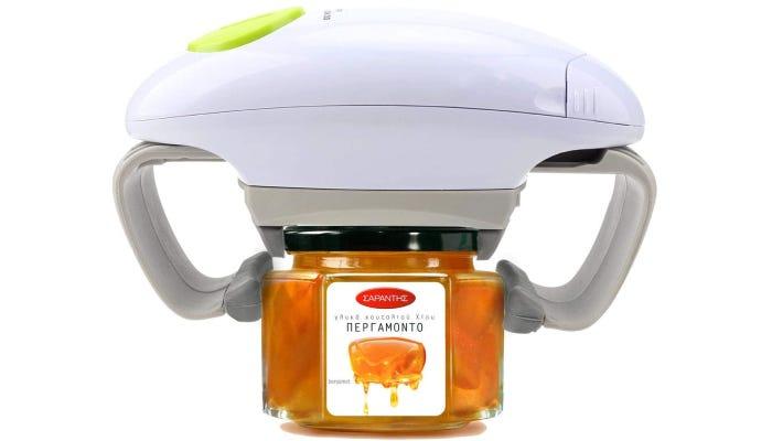 An electric jar opener is shown gripping a glass gar.