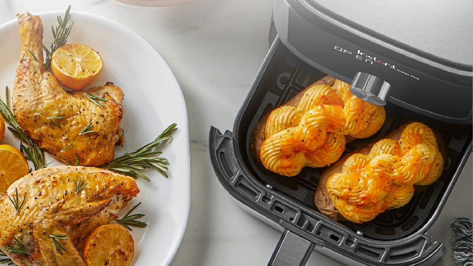 An air fryer with two fancy baked potatoes and a side plate of chicken thighs with rosemary and halved lemons.