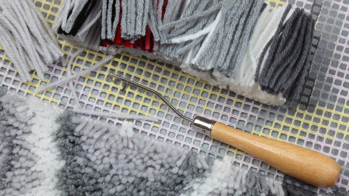 canvas, cut yarns, latch-hook craft ready to create a gray rug