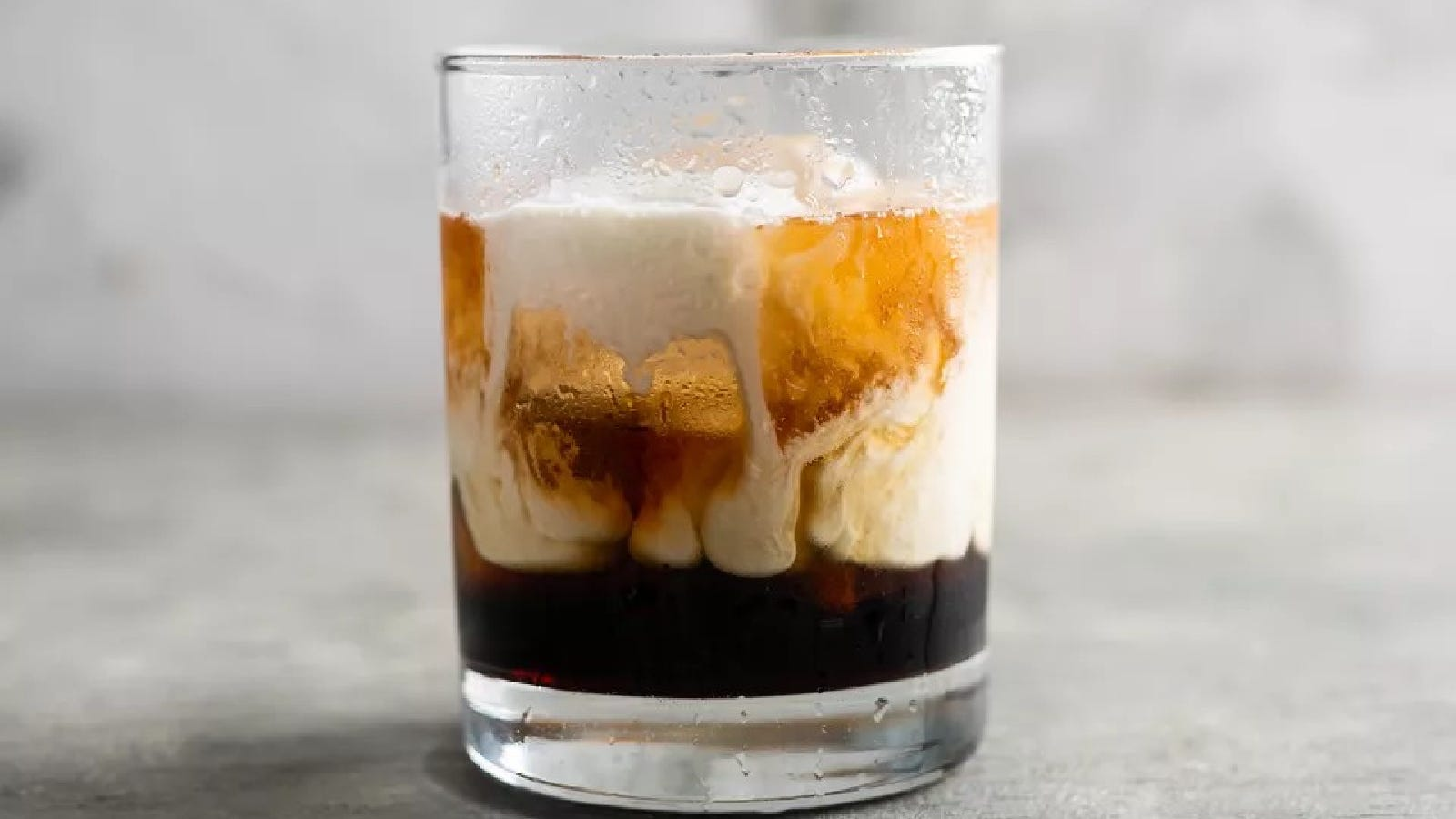 A short rocks glass with one large ice cube, filled with a recently poured white Russian cocktail.