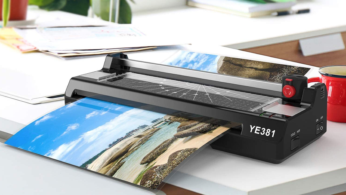 black rectangular laminator machine on a desk in the process of laminating a vacation photo