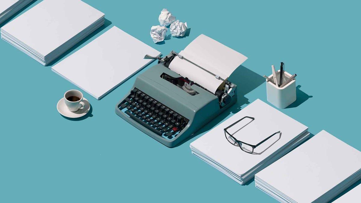 Синие пишущие машинки на бирюзовом синем фоне с бумагой, ручками и кофейной кружкой.