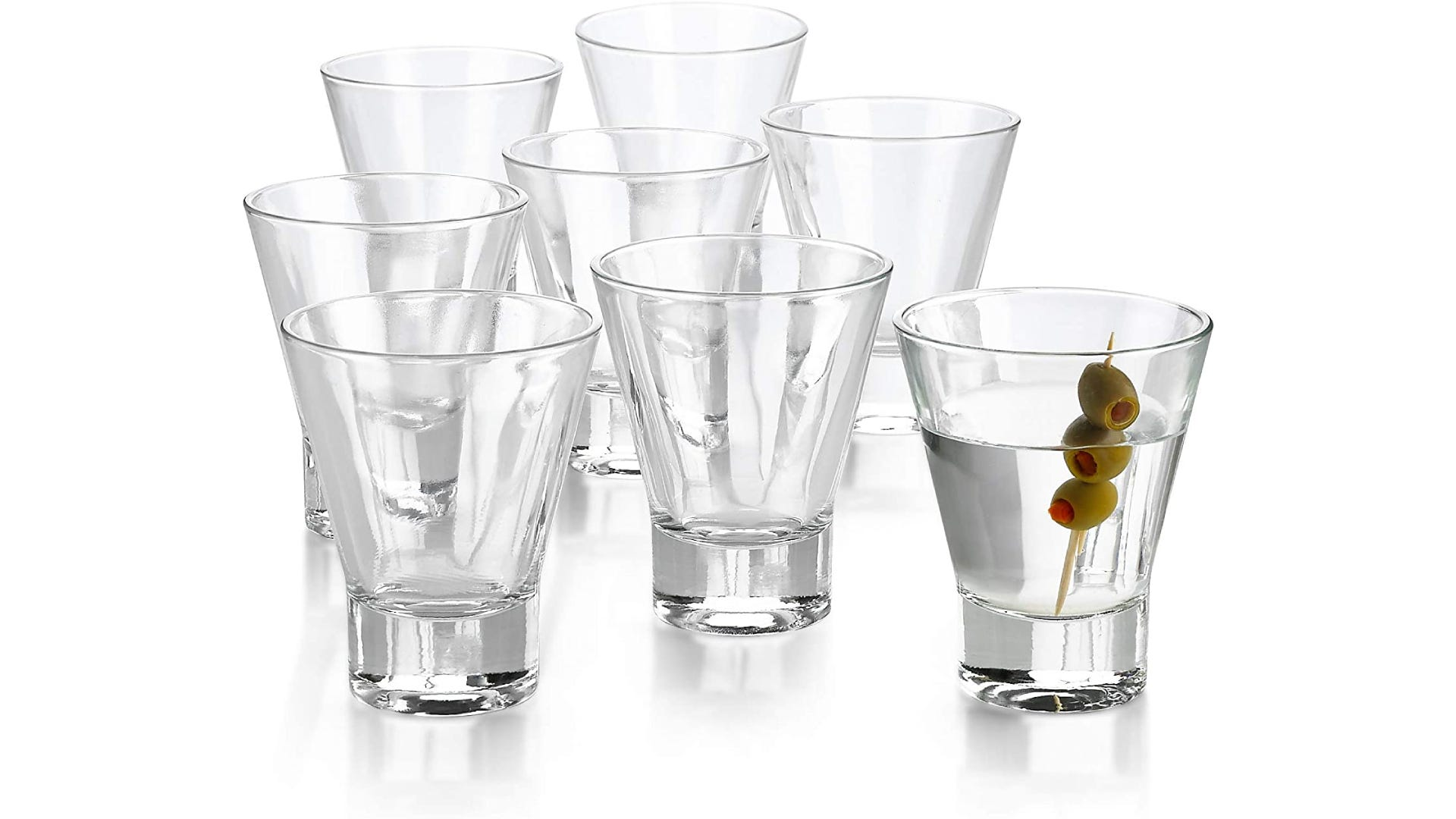 Eight conical clear glasses, one filled with olives and clear liquid.