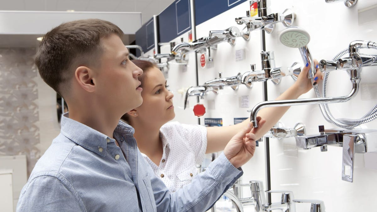 A man and woman looking at bathroom hardware and fixtures.