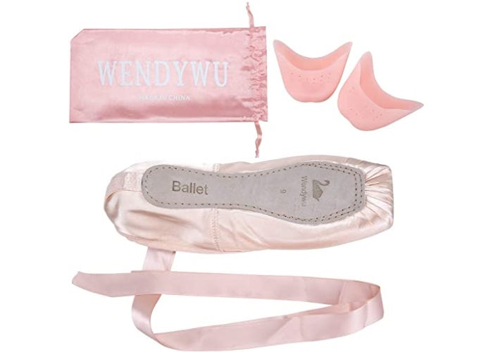 sole view of ballet shoe with ribbon beside pink brand bag