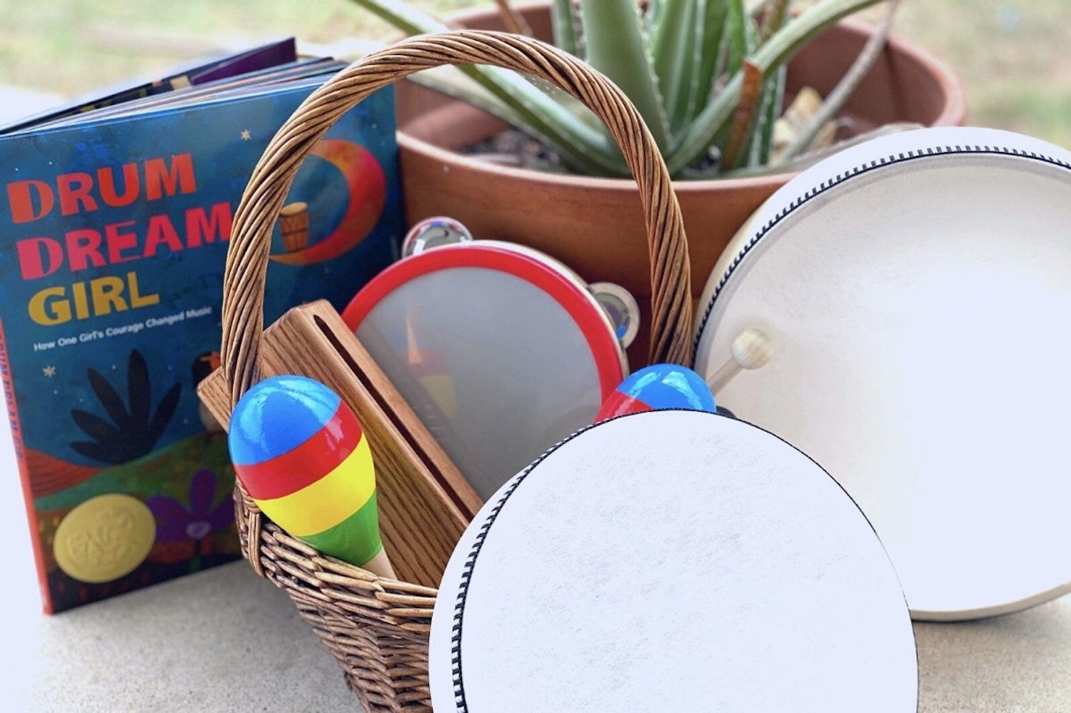 """A book titled """"Drum Dream Girl,"""" a basket with percussion instruments, and two small drums"""