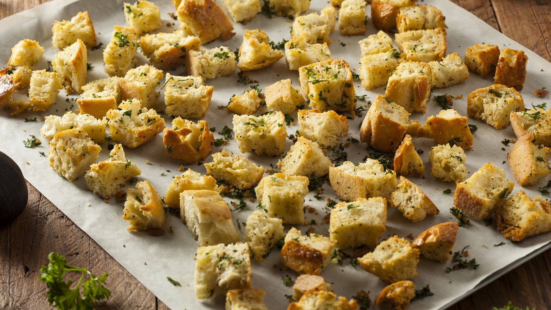 Seasoned homemade croutons on a sheet of parchment paper.