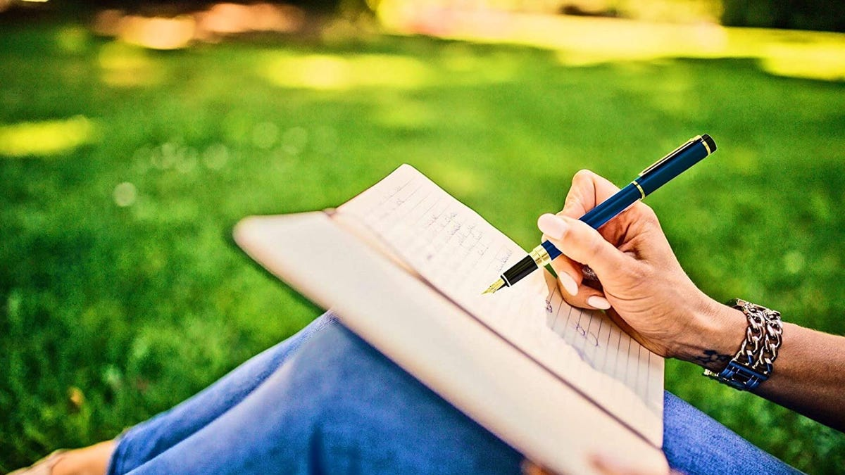 A woman wearing silver chain bracelet writes in a notebook with a blue and gold fountain pen while sitting in the grass.