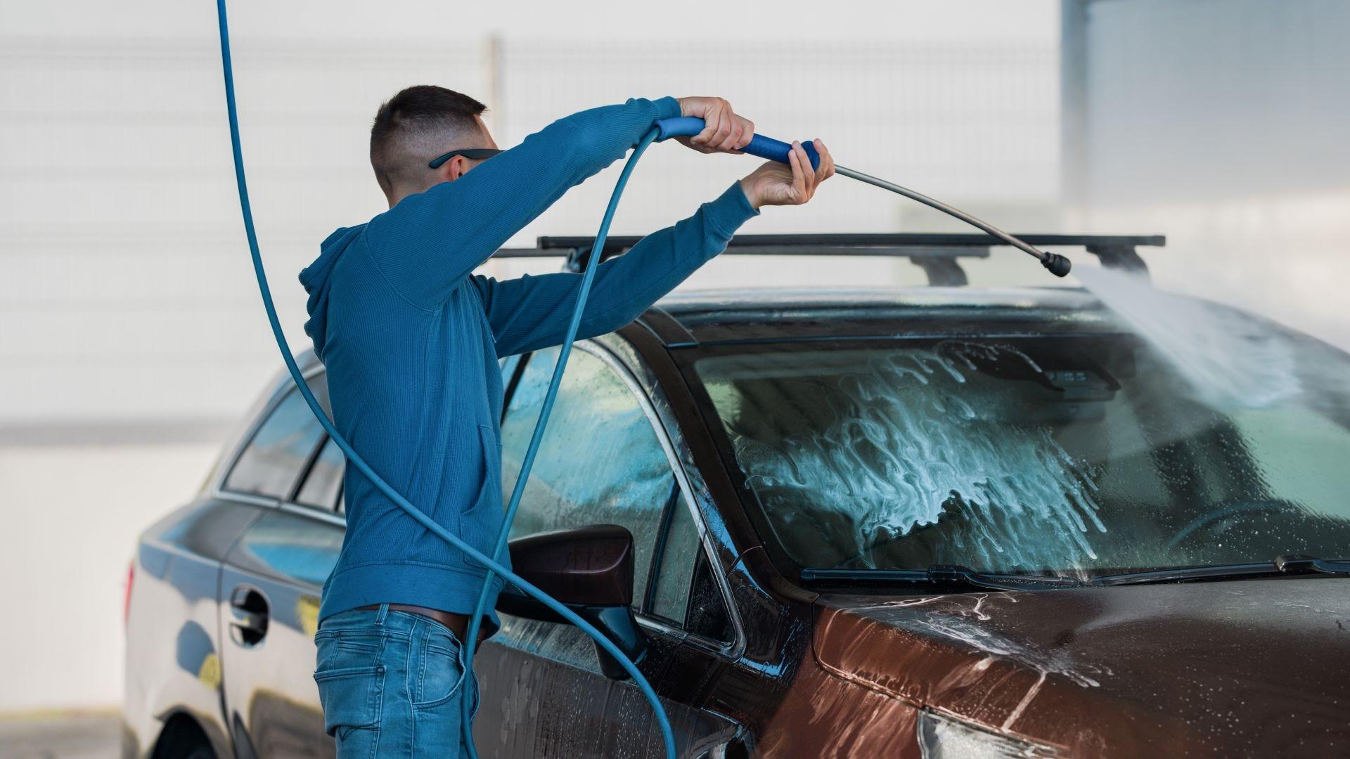 A man washing his car at a self-serve car wash.