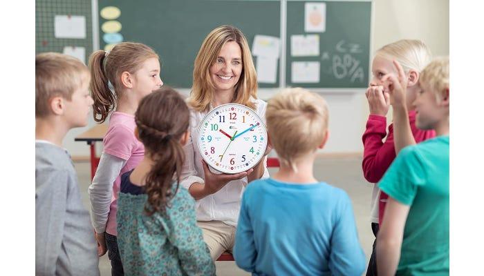 Female teacher holding clock. Students surround her.