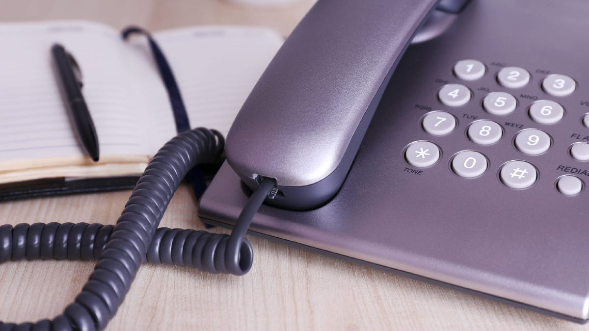 a corded phone on a desk by an open notebook
