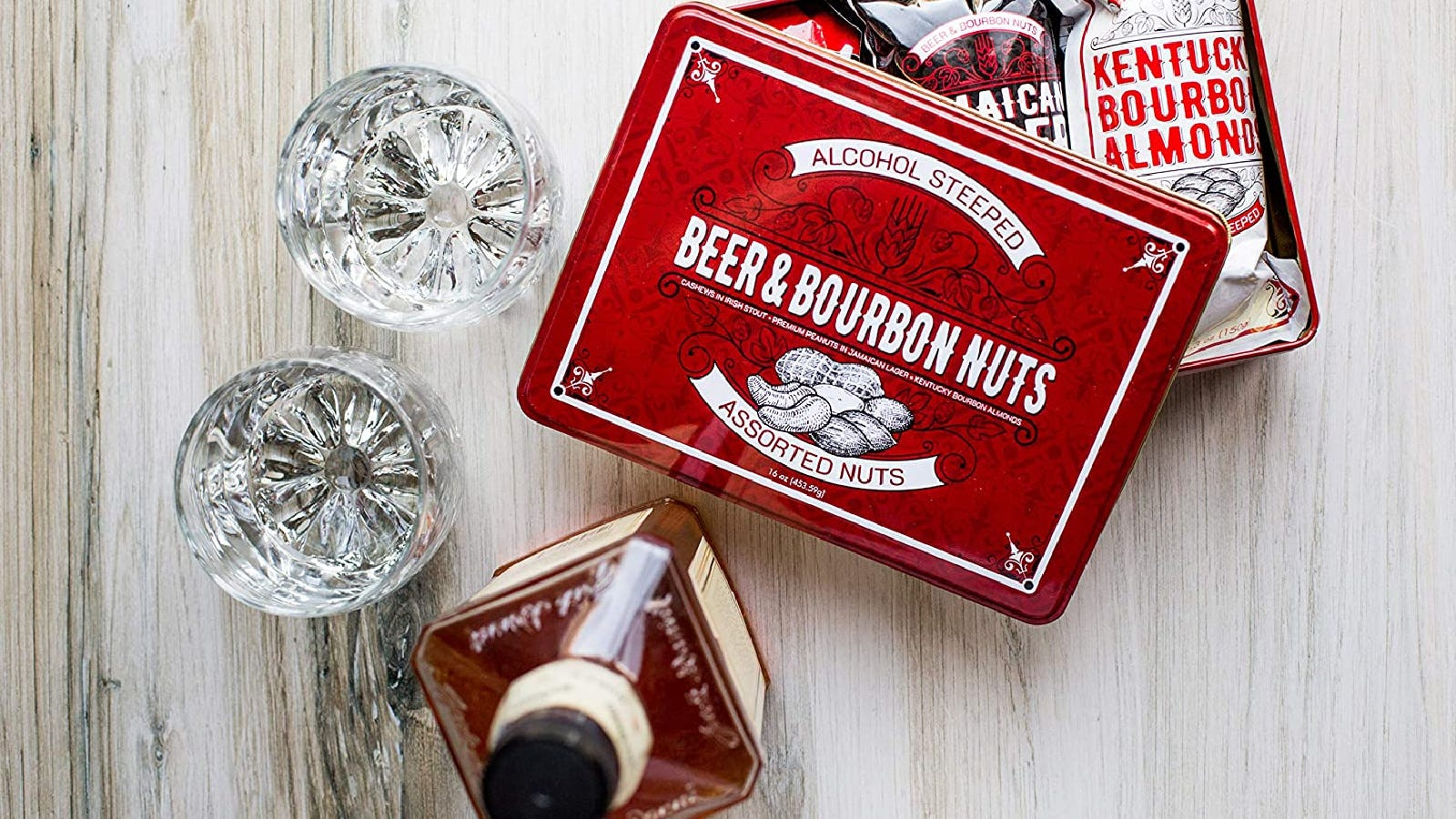A tin box of beer & bourbon nuts, next to an aged bottle of whiskey and two glasses.