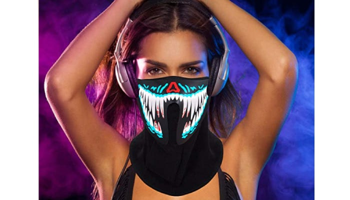 A woman wearing headphones and an LED mask with a teeth design.