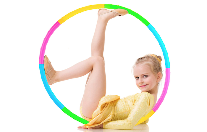 young girl in a yellow leotard posing inside a brightly multicolored hula hoop