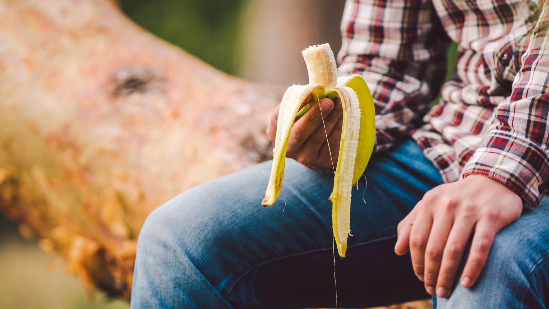 Man eating a banana on a hike.