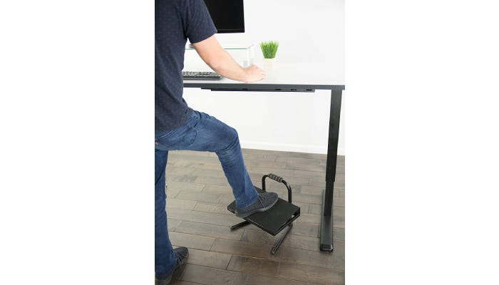 A guy using a foot rest while using his standing desk.