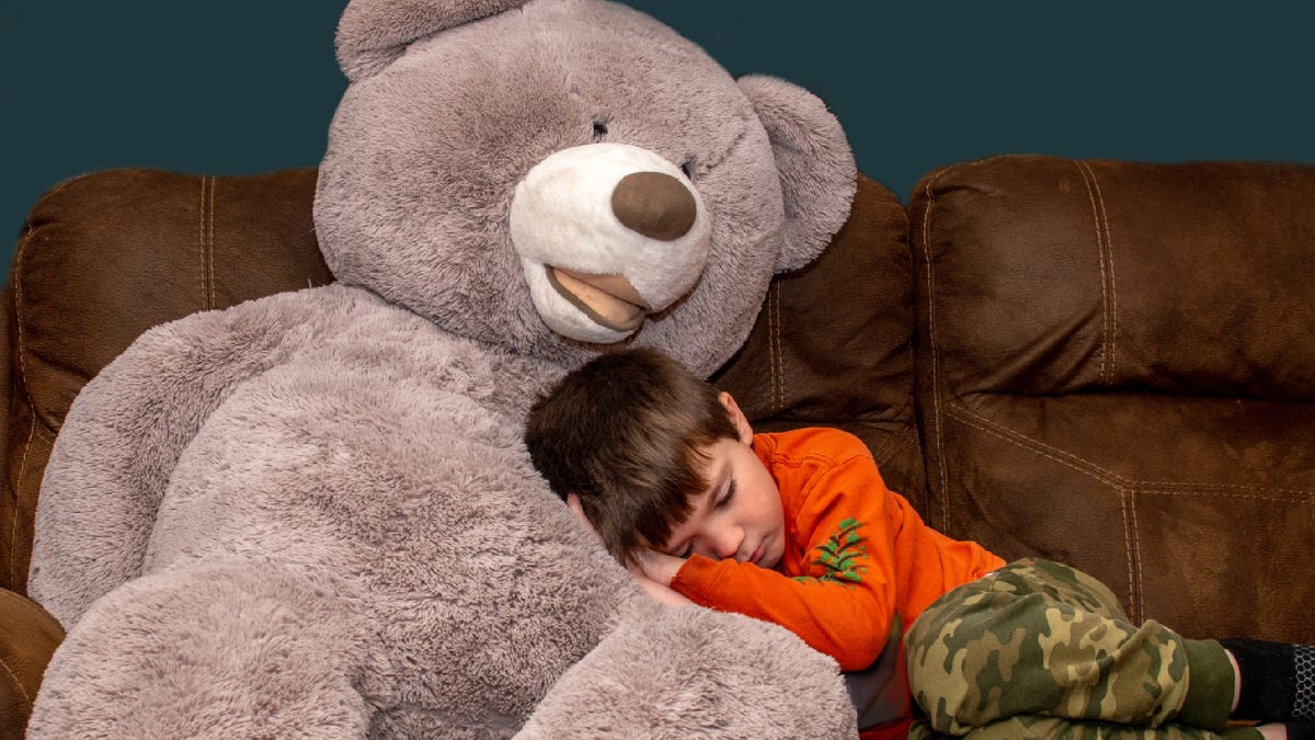 a young boy resting his head on a giant stuffed teddy bear