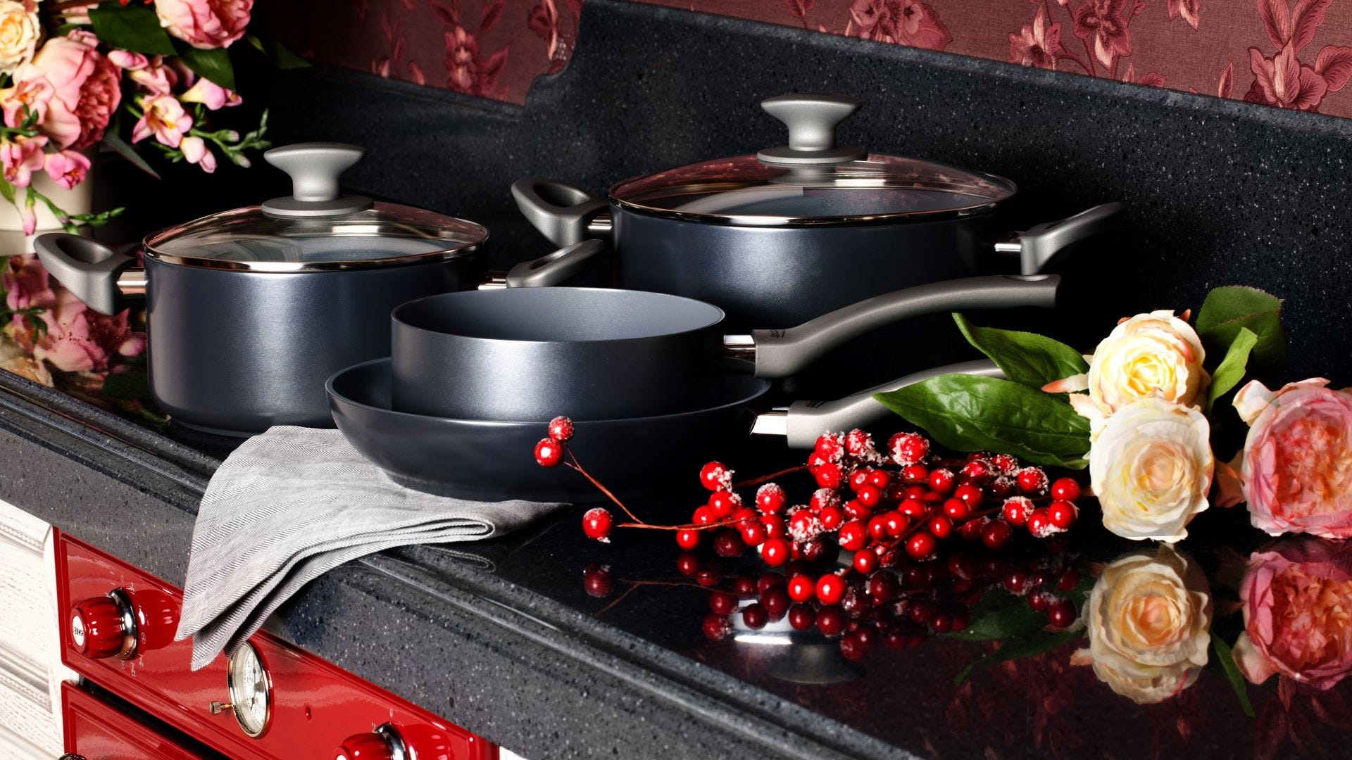 Gray pots and pans on a stove in a red kitchen.