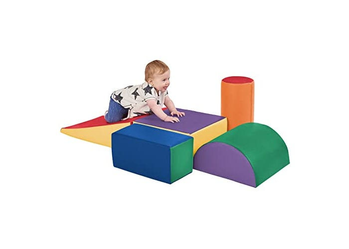 young toddler climbing on colorful foam slide with blocks