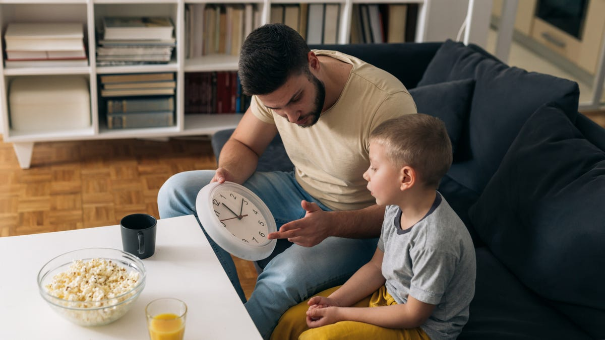 a father teaching his son to tell time on an analog clock