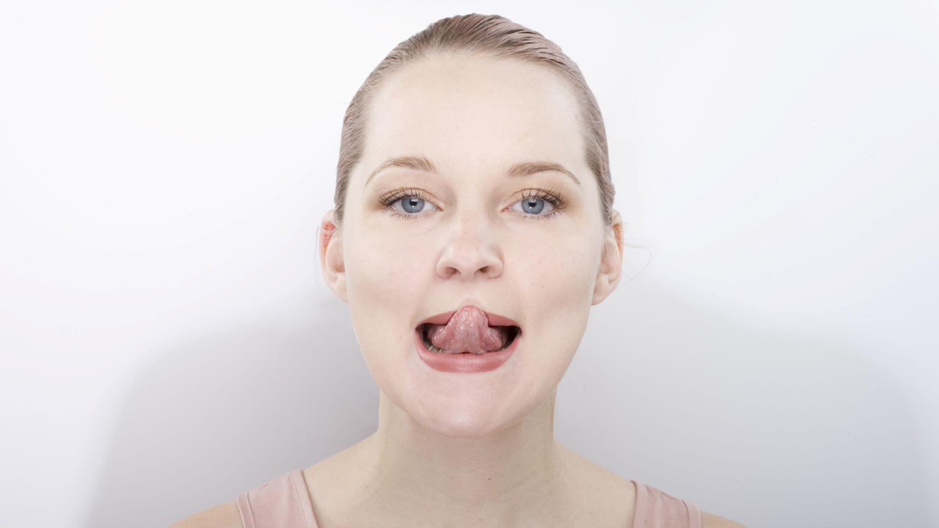 A woman using the tongue roll face yoga pose to boost collagen in her lips.
