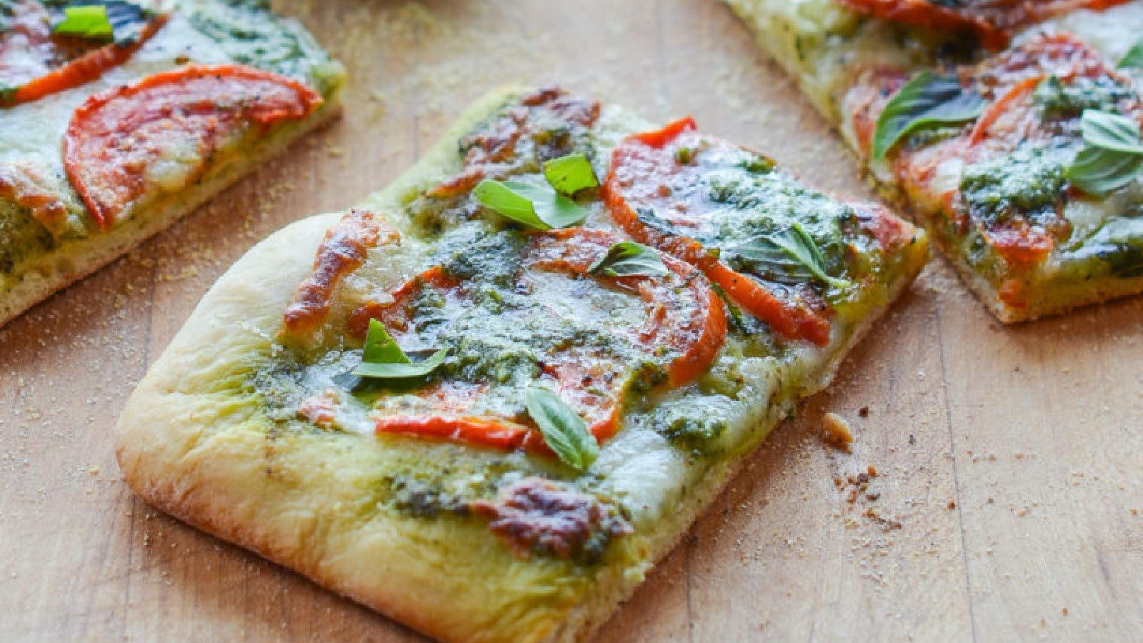 A sheet pizza topped with pesto, sliced tomatoes and mozzarella cheese.