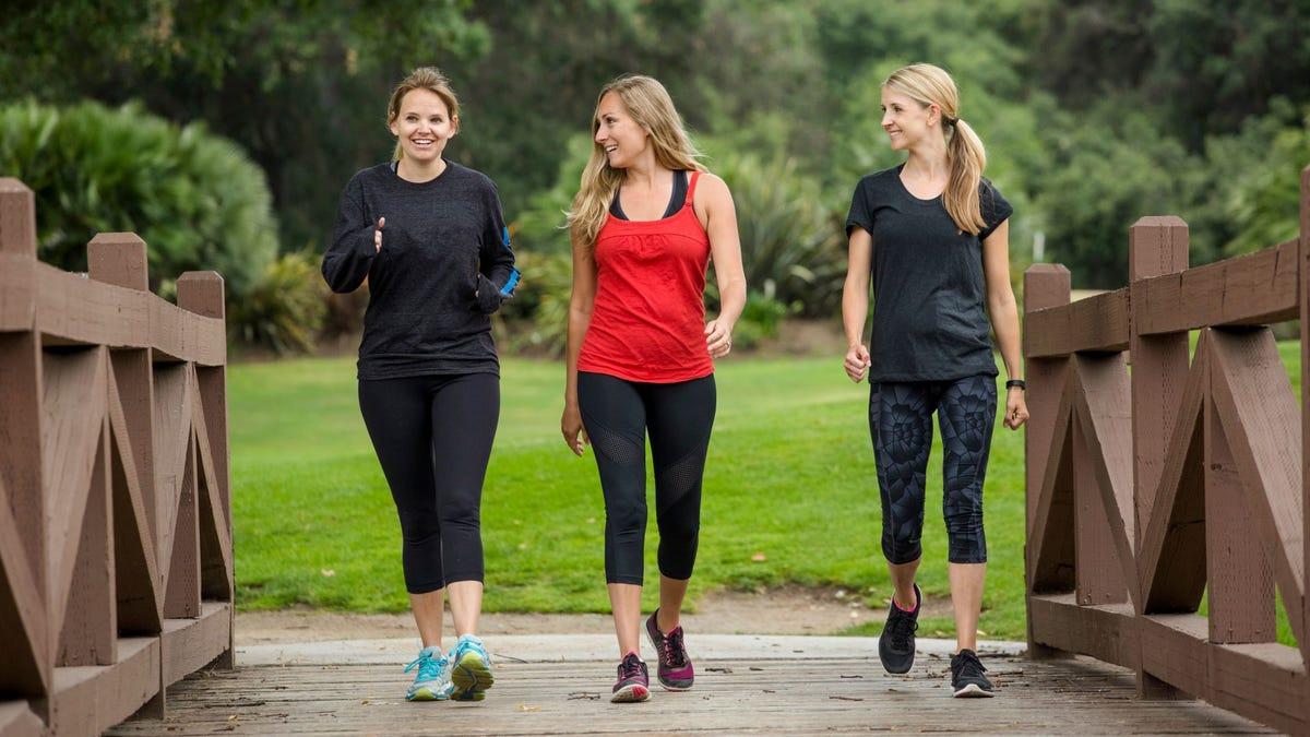 Three women walking in a park.
