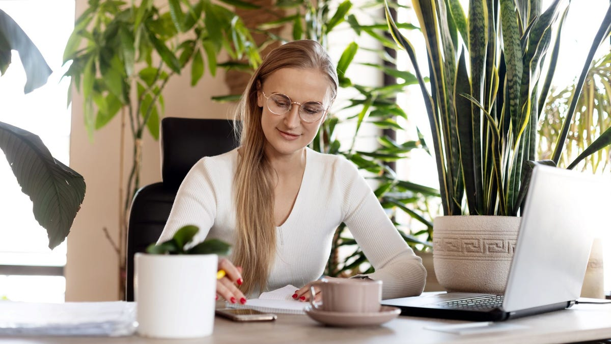 A woman working at a desk surrounded by plants.