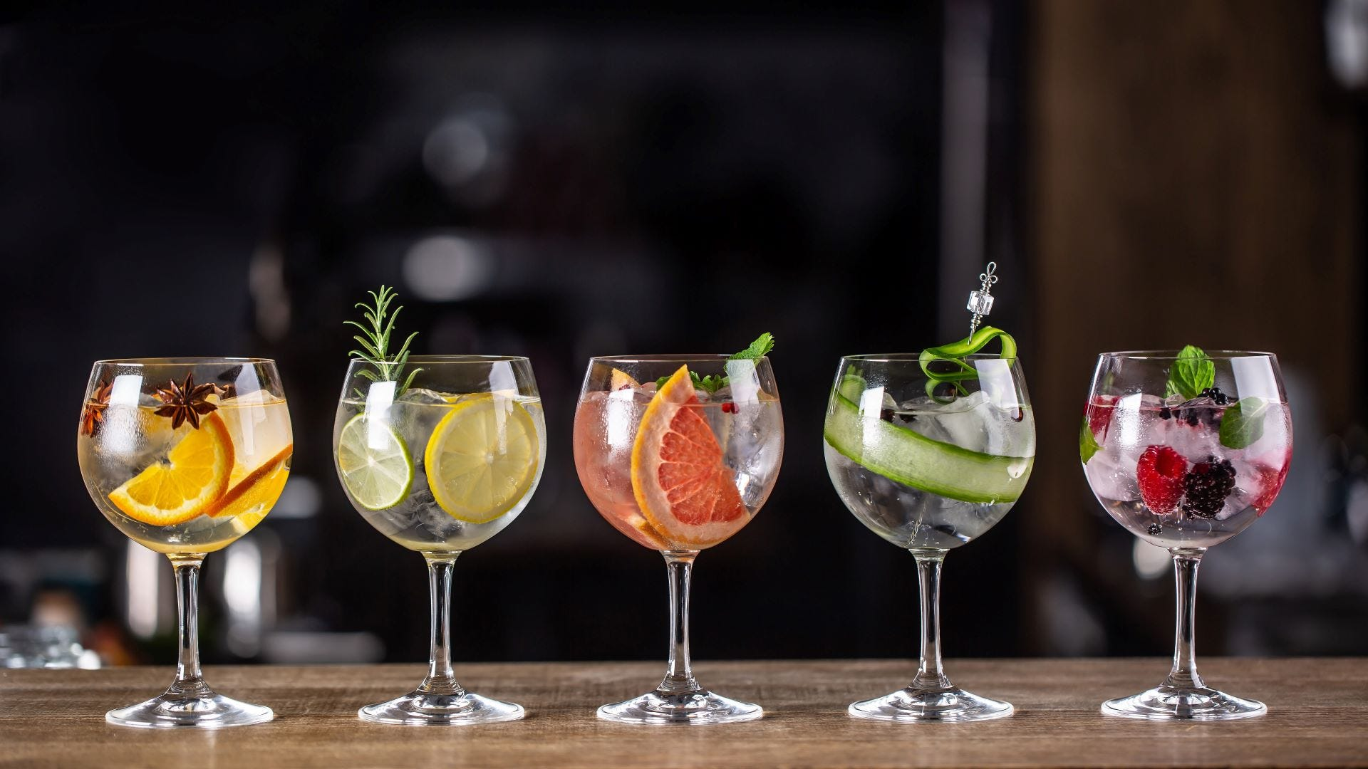 Five cocktails on a bar with different garnishes.