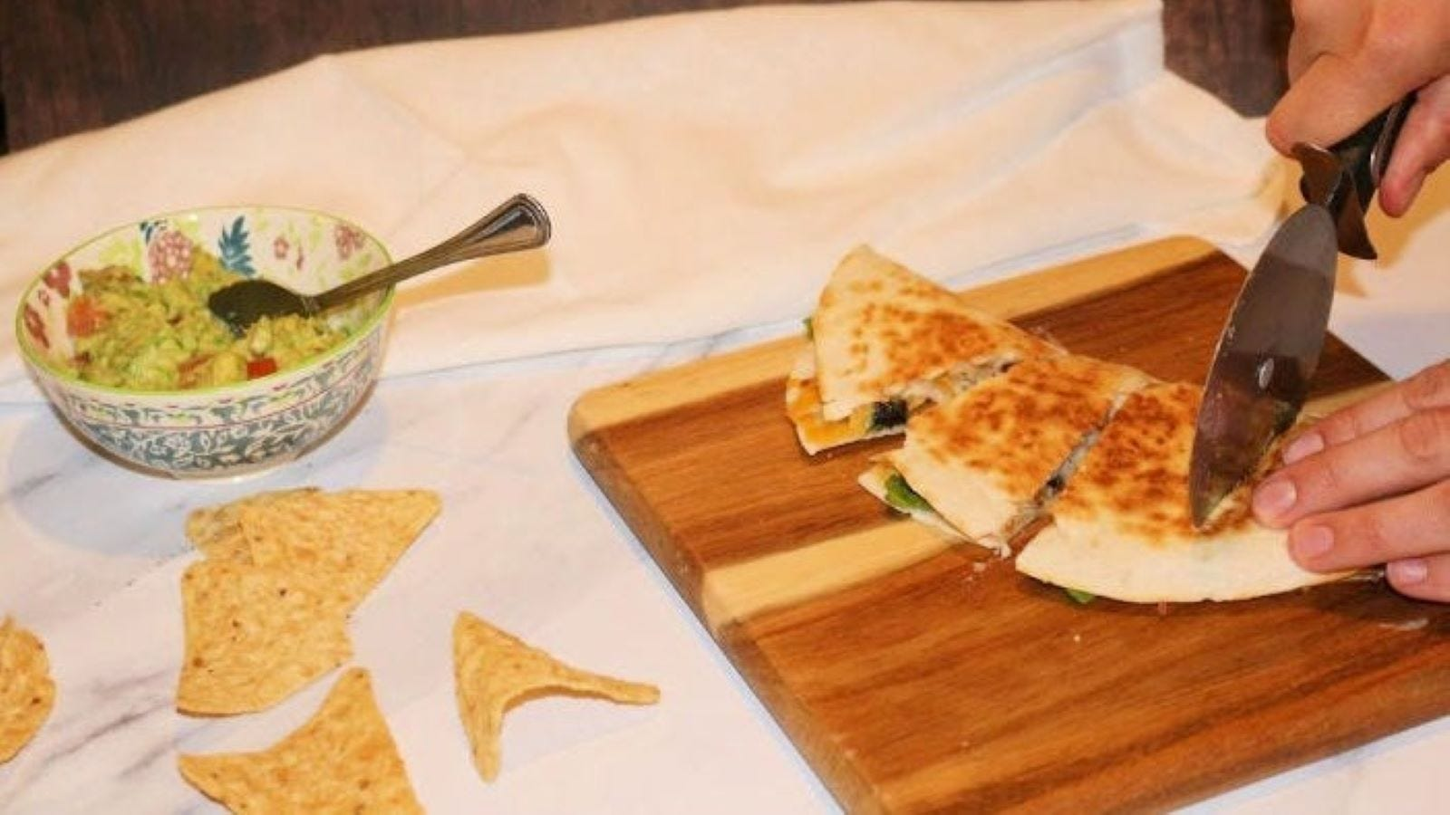 Someone slicing cheese quesadillas on a cutting board.