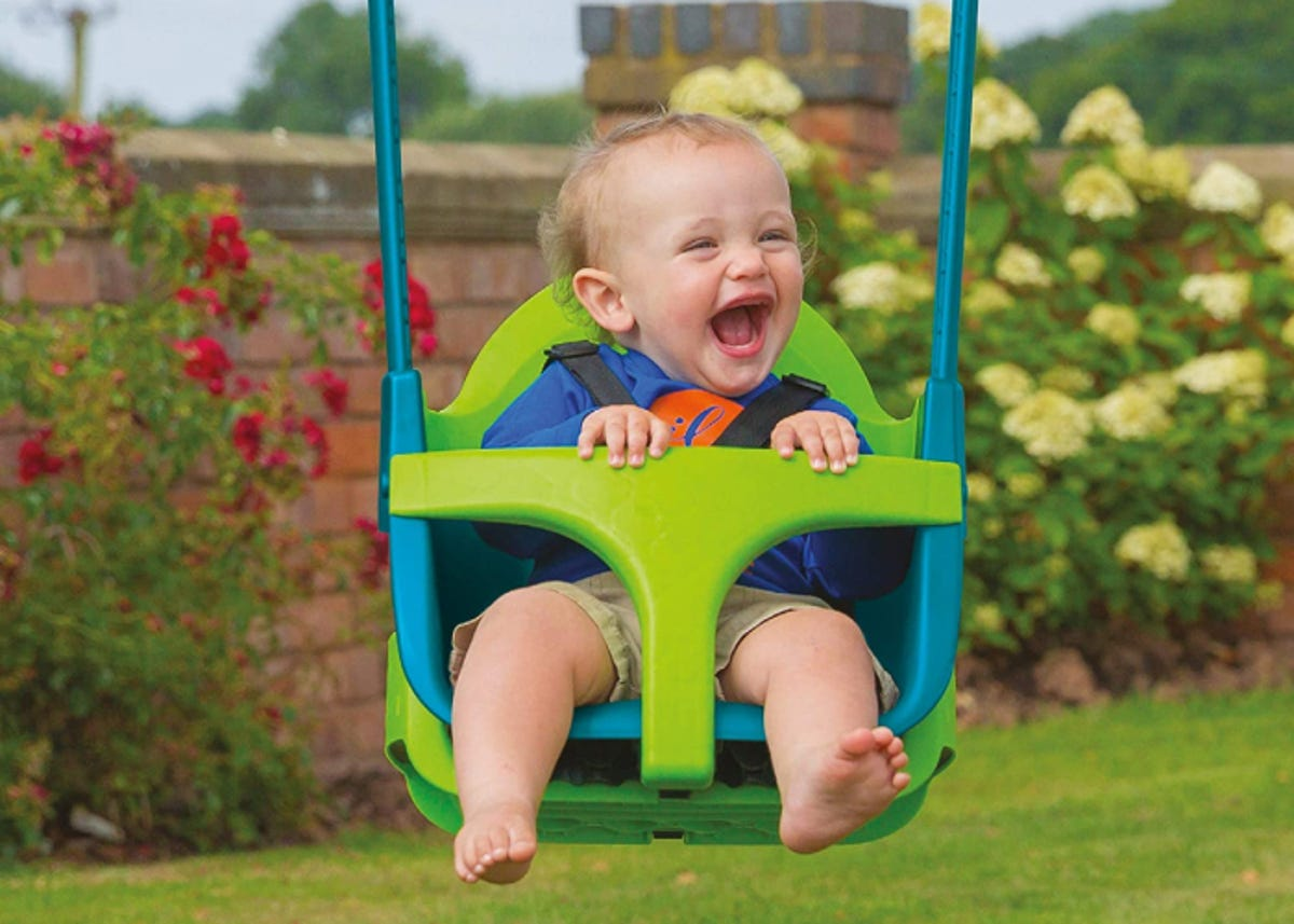 a super happy smiling baby boy in a baby swing