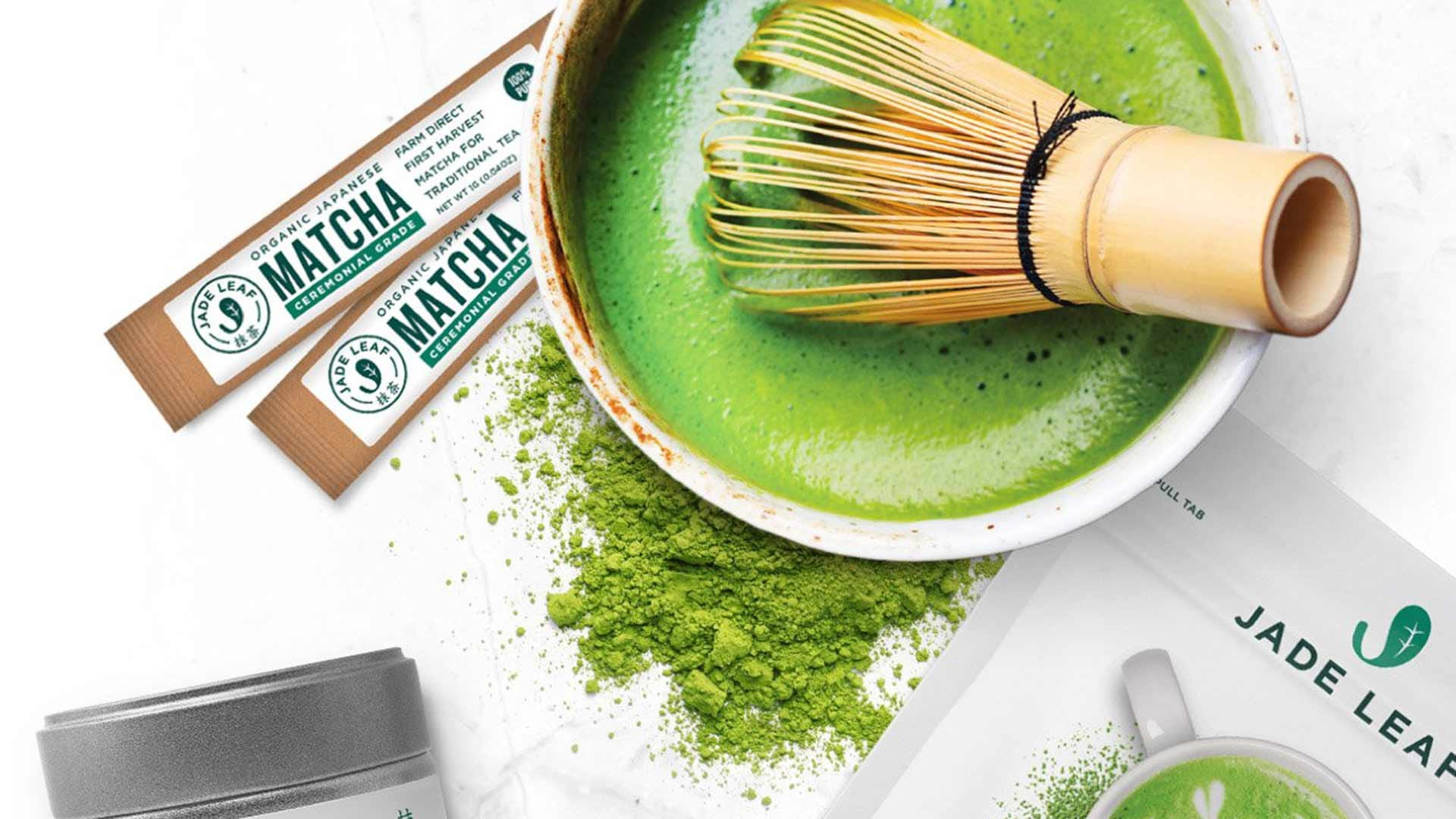 A fresh cup of matcha tea with a traditional bamboo whisk.
