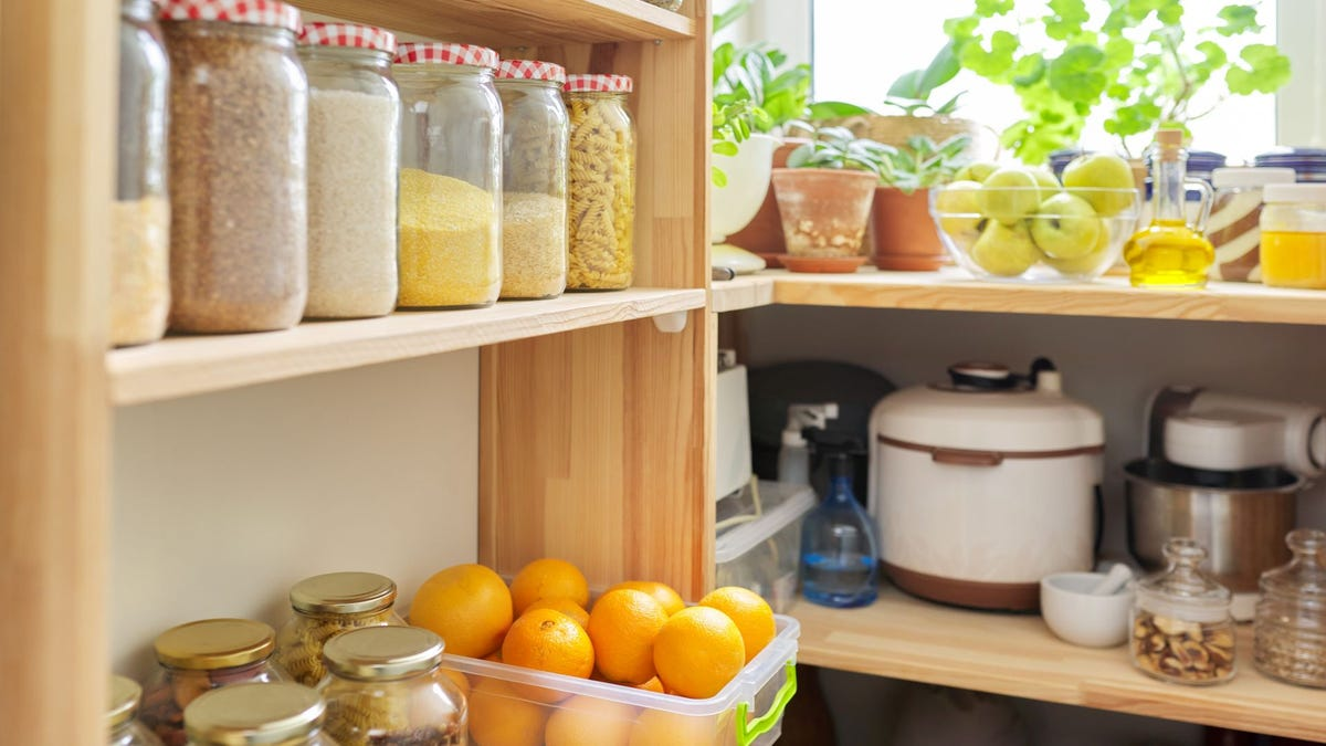 A pantry stocked with dry goods, fruit, and appliances.