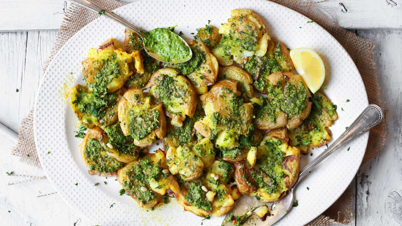 A large oval plate topped with roasted smashed potatoes, topped with pesto and pine nuts.