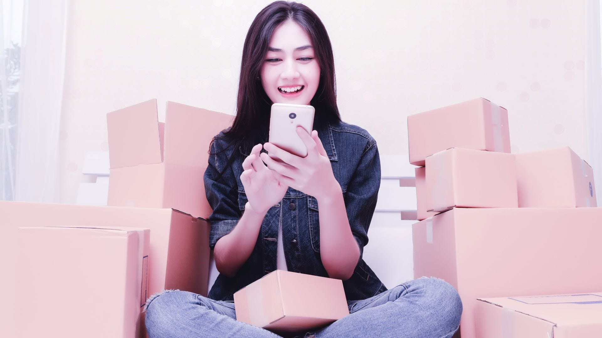 A woman surrounded by moving boxes, reading reviews of moving companies on her phone.