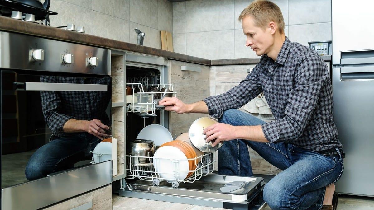 A man loading a dishwasher.