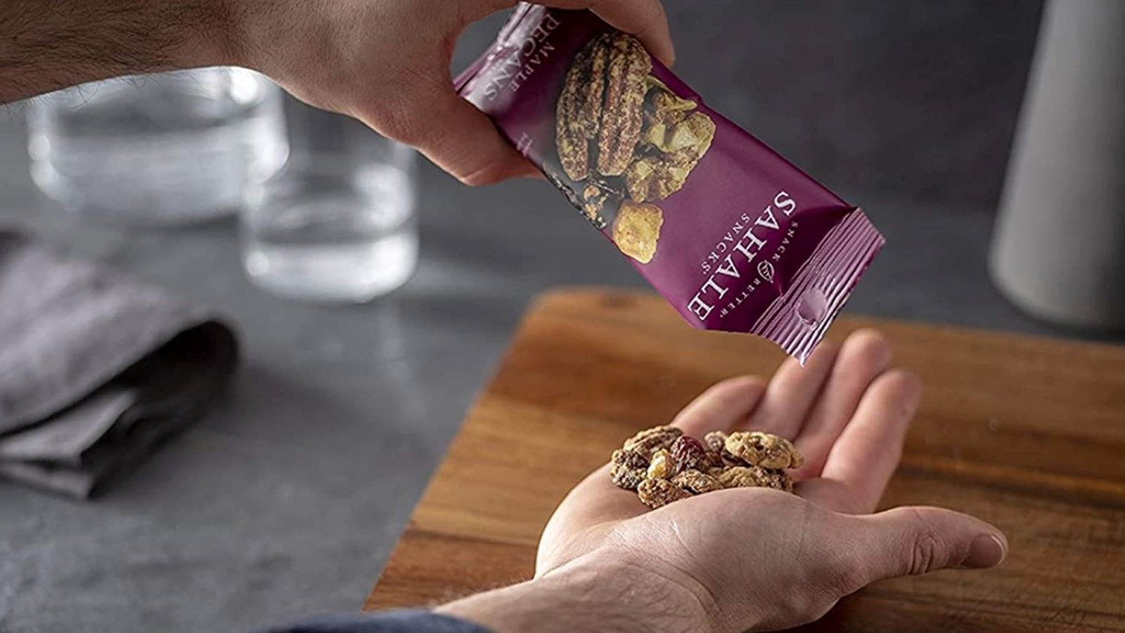 Someone sprinkling Sahale Maple Pecans in their hand out of a snack pack.