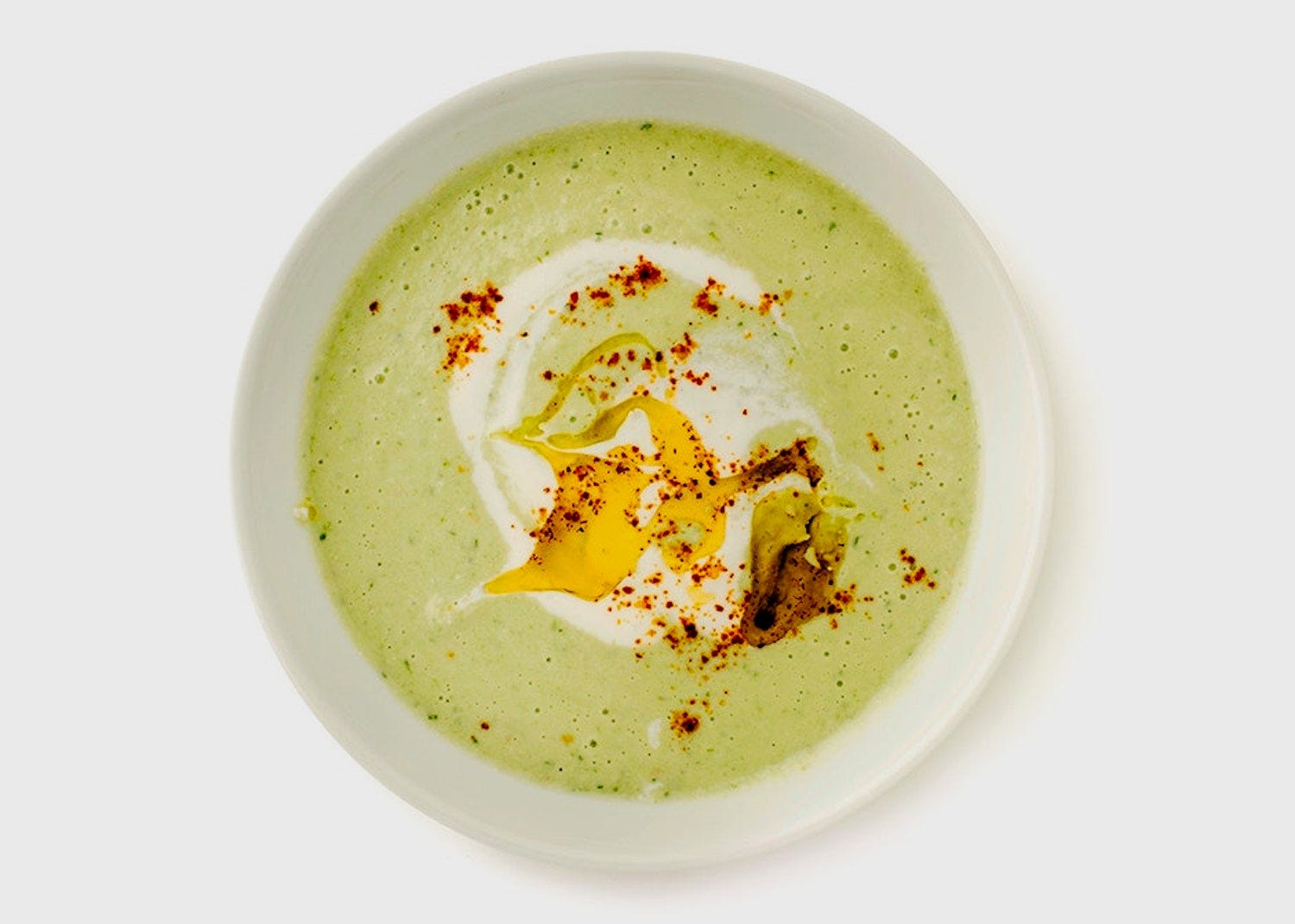 Overhead view of a bowl of green gazpacho
