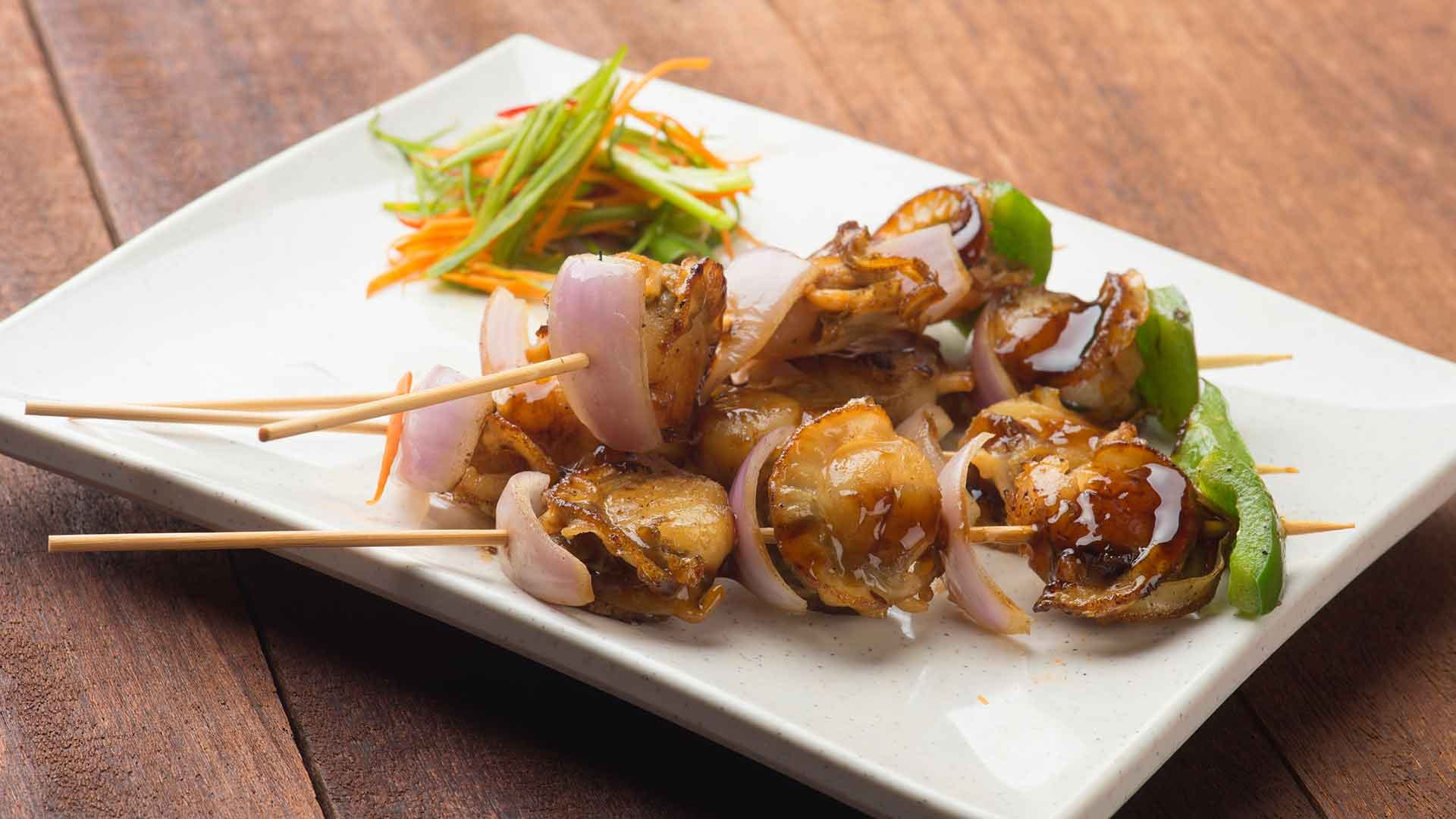 Grilled scallops skewered resting on a rectangle white plate.