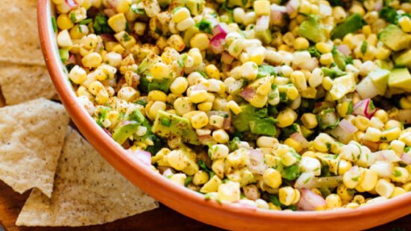 A bowl of fresh corn salsa using with a side of tortilla chips.