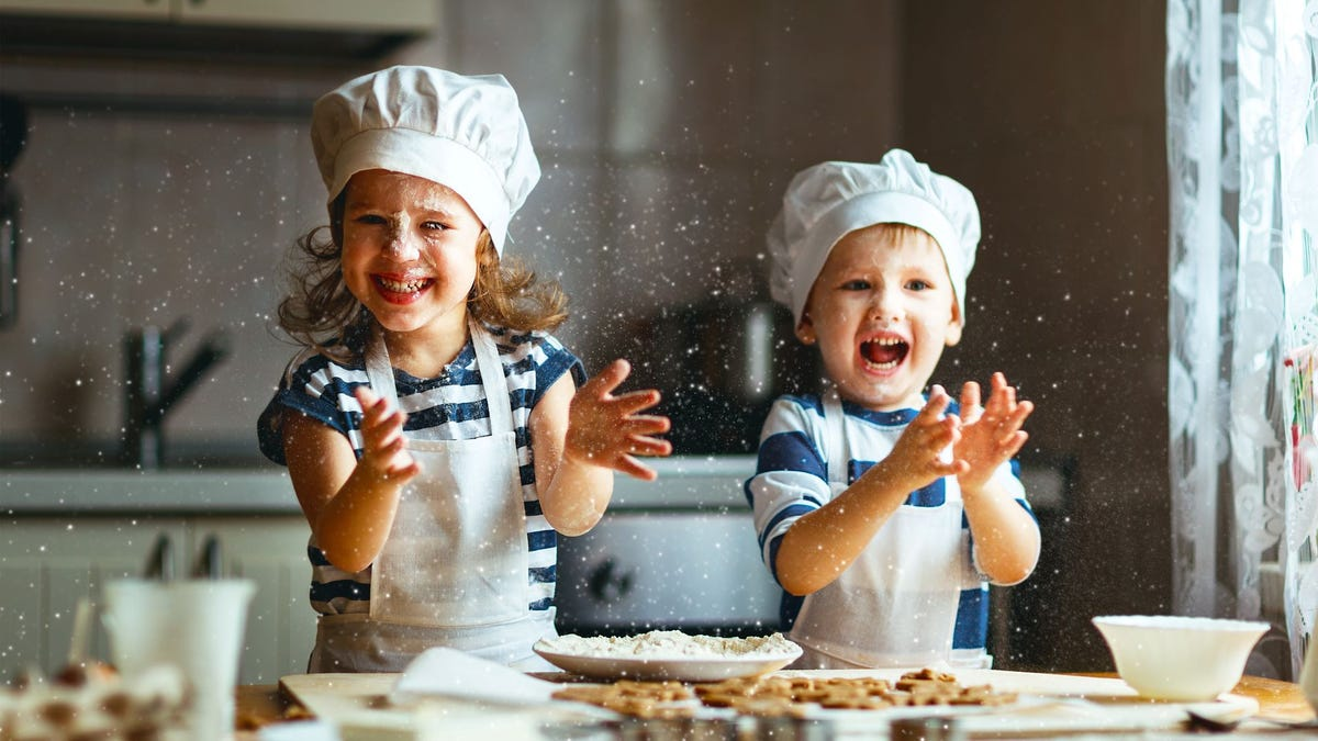 A boy and girl wearing chef's hats covered in flour.