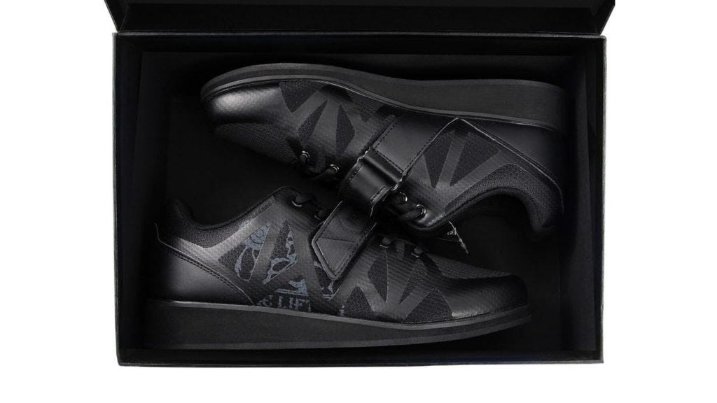 a pair of black weightlifting shoes in a shoe box