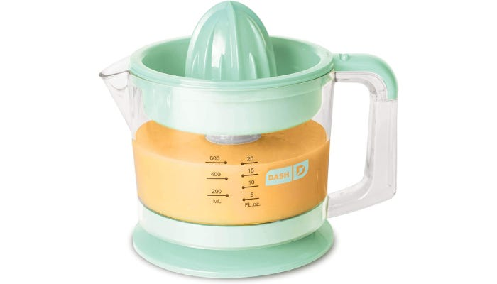 Small pitcher with cone juicer lid in place. Filled with orange-colored juice