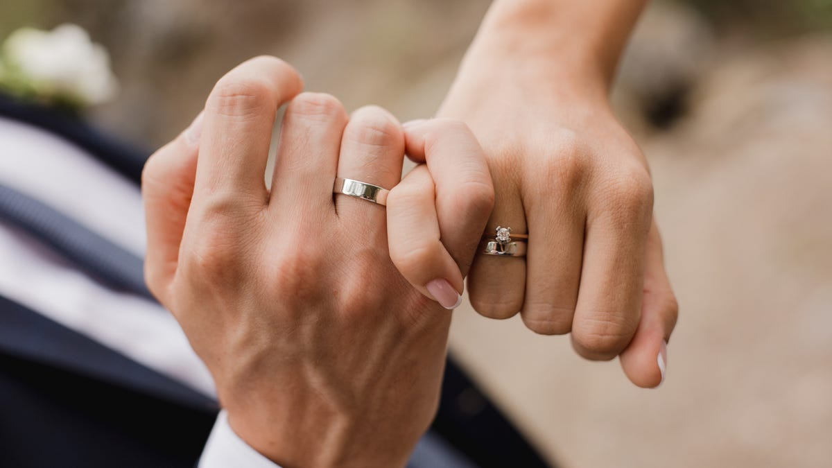 Close up picture of intertwined hands with wedding rings.